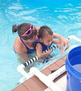 Young student Timothy swims with Miss Becky.